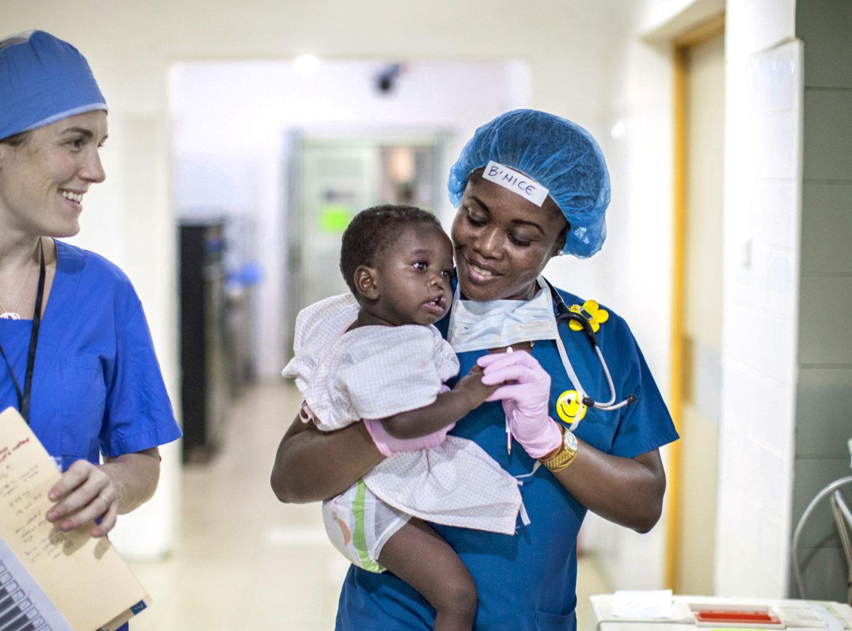 volontär bär en liten pojke till operation för läppspalt