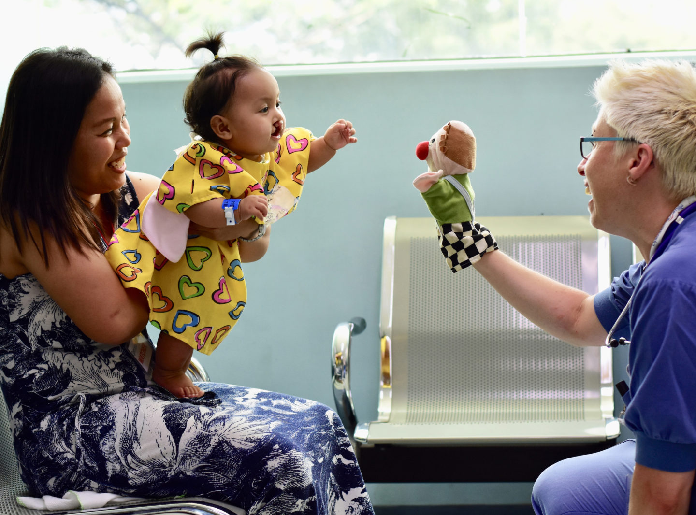 volontär andréa berg leker med ett barn innan operation