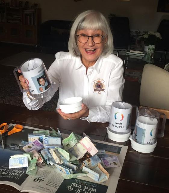 Marianne visar pengarna som hon samlat in till Operation Smile